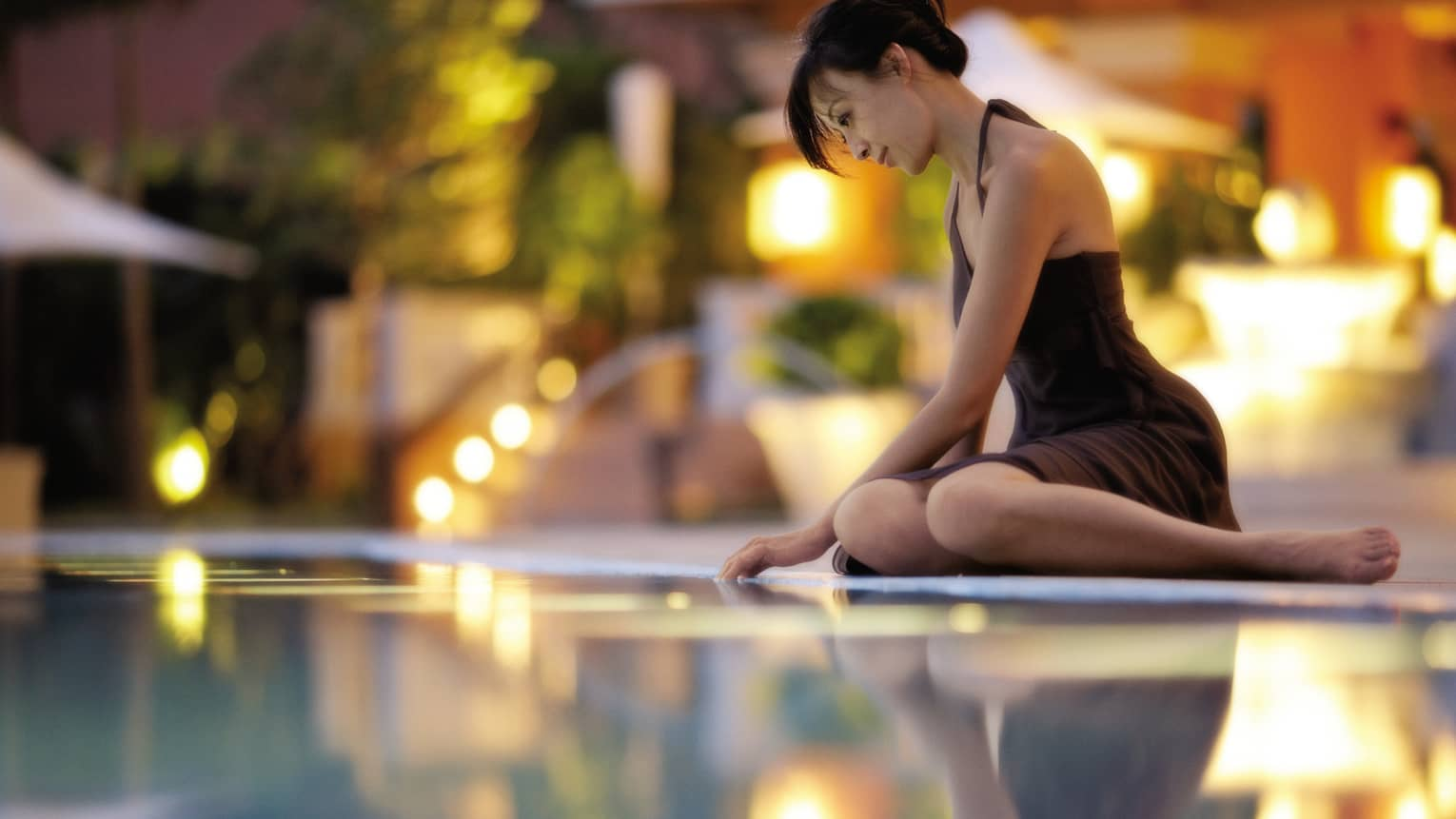 Woman wearing black dress sits on edge of pool, runs fingers over water
