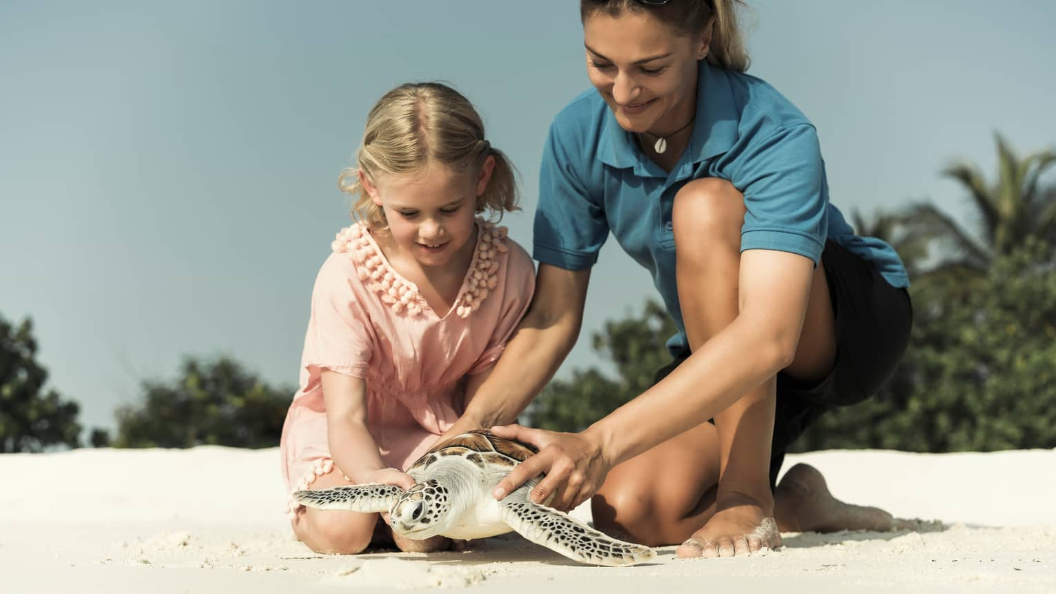 Hotel staff, young girl hold sea turtle over white sand beach