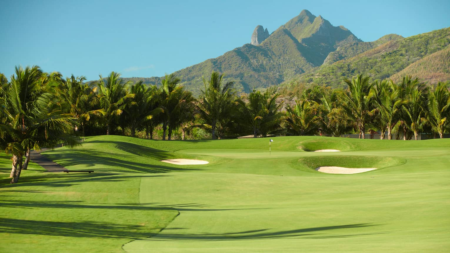 Fifteenth hole rolling golf course green dotted by two sand traps, mountain backdrop