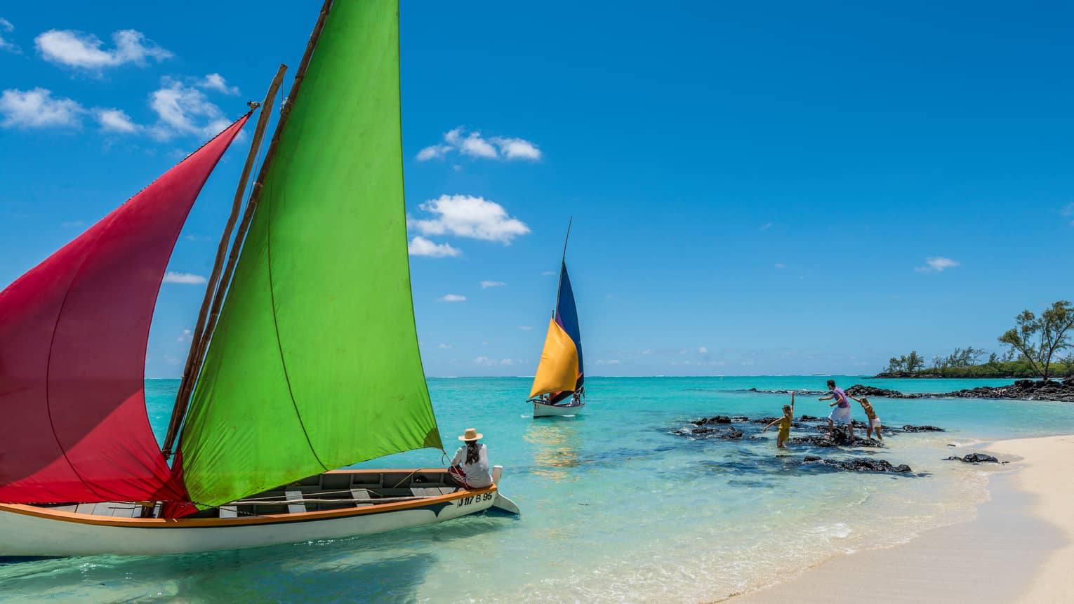 Family plays on beach, rocks in front of two sailboats with colourful sails