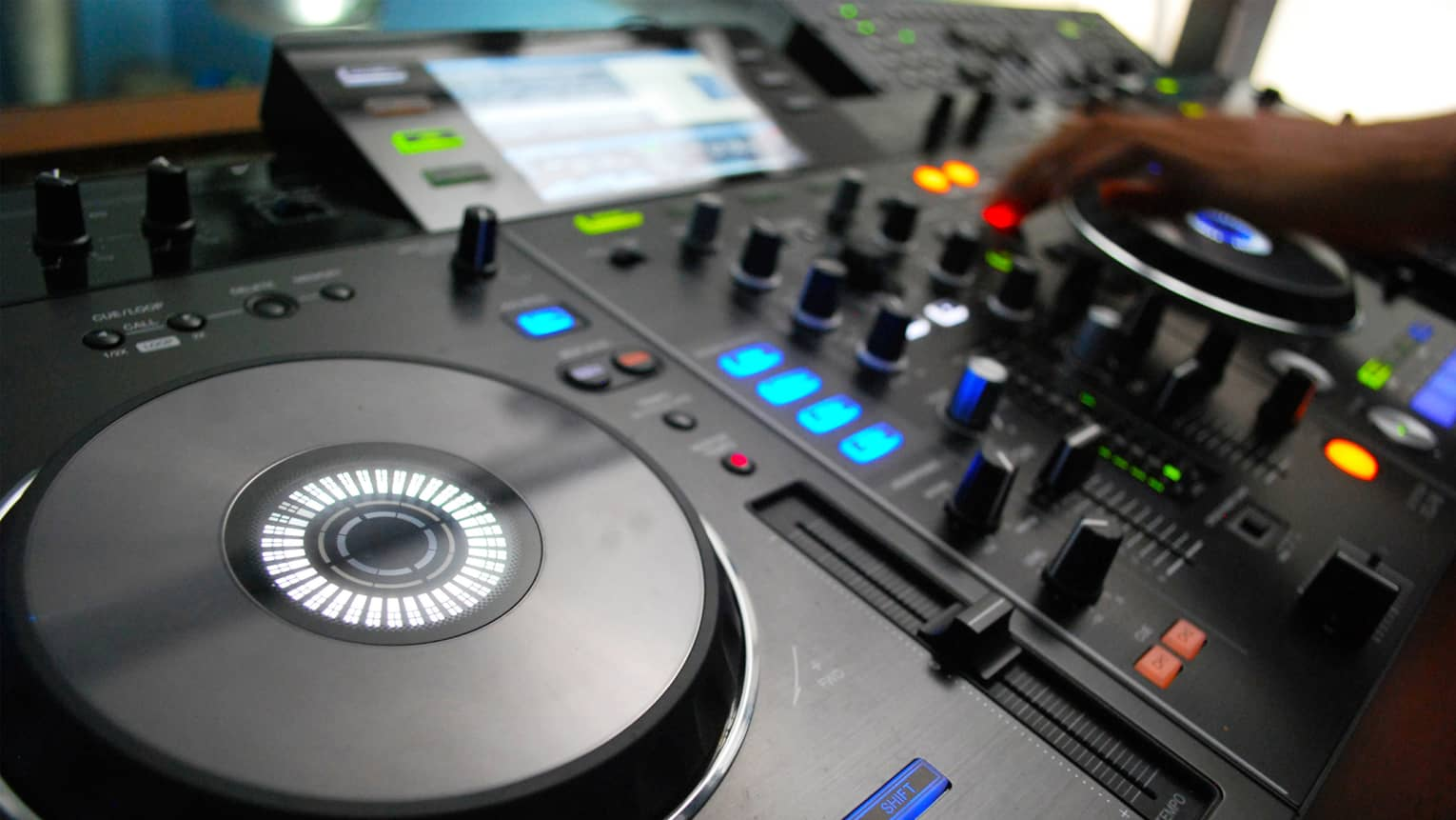 Close-up of DJ console discs, buttons, lights, hand adjusting levels