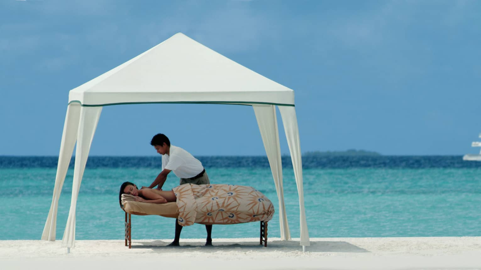 Masseuse gives woman massage on table under white canopy on atoll, yacht in background