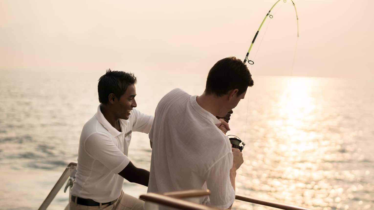 Two men holding poles reel in deep sea fishing lines at side of boat