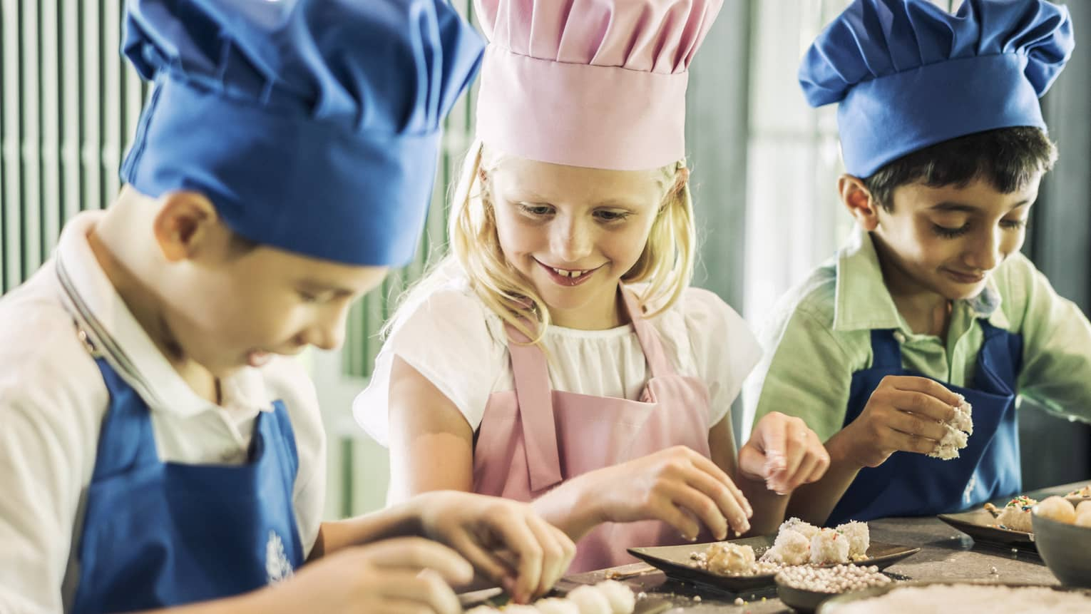 Three children in chef hats, aprons roll pastries at counter