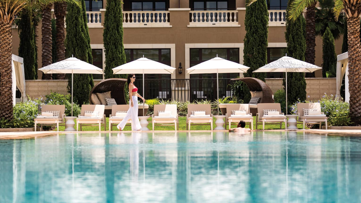 Woman walks by row of white patio chairs, umbrellas on outdoor swimming pool deck