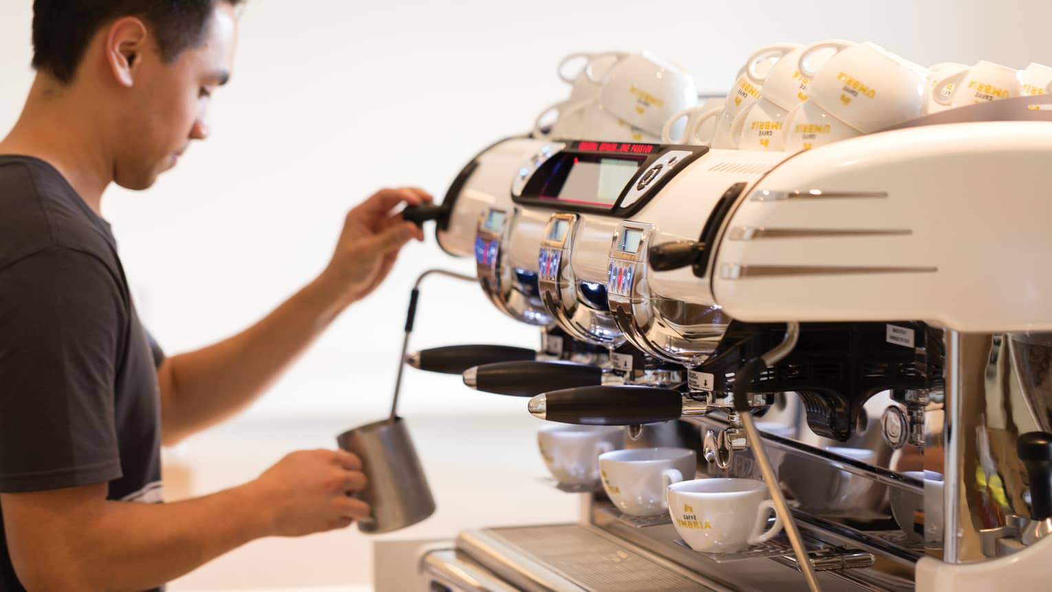 Barista stands in front of espresso machine lines with small white mugs, froths milk in silver jug