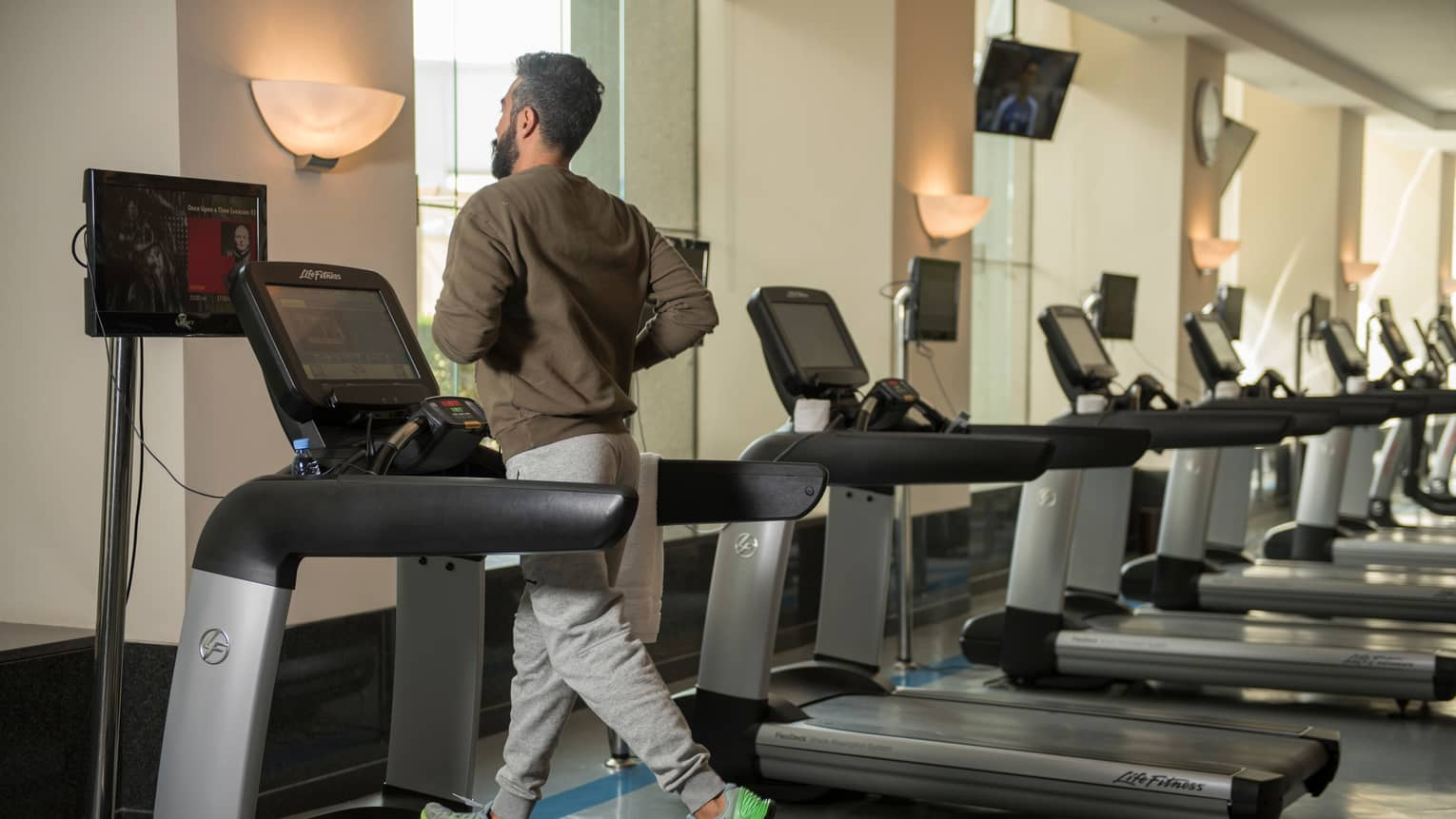 Back of man in sweatshirt and sweatpants as he runs on treadmill in gym next to row of cardio machines