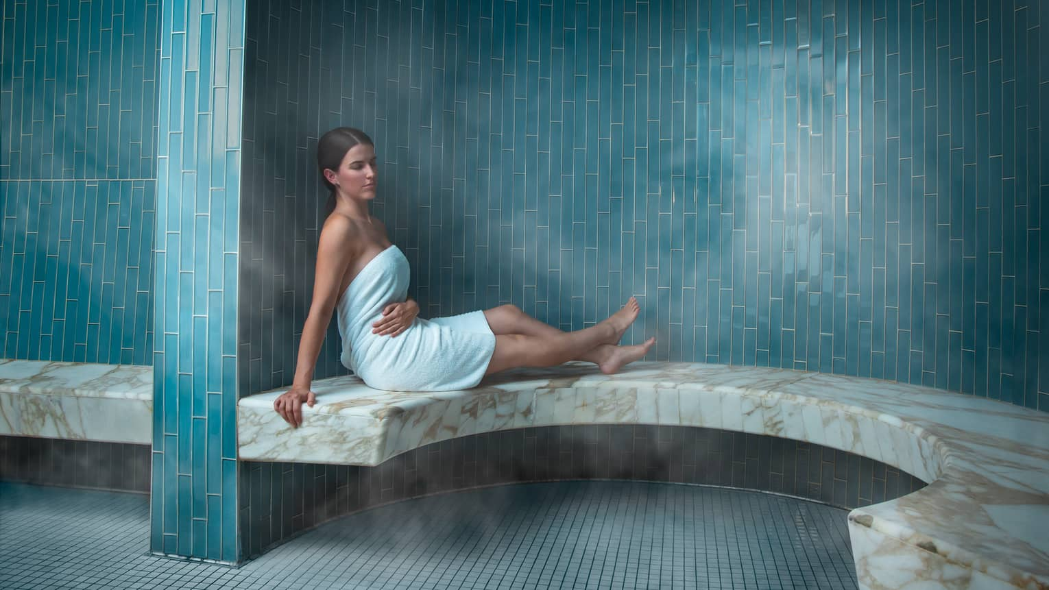 Woman in towel lounges on marble bench in spa steam room