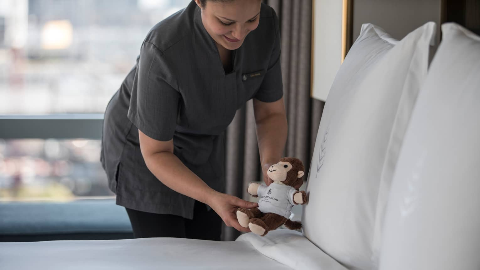 Hotel staff sets small stuffed monkey toy down on made hotel bed