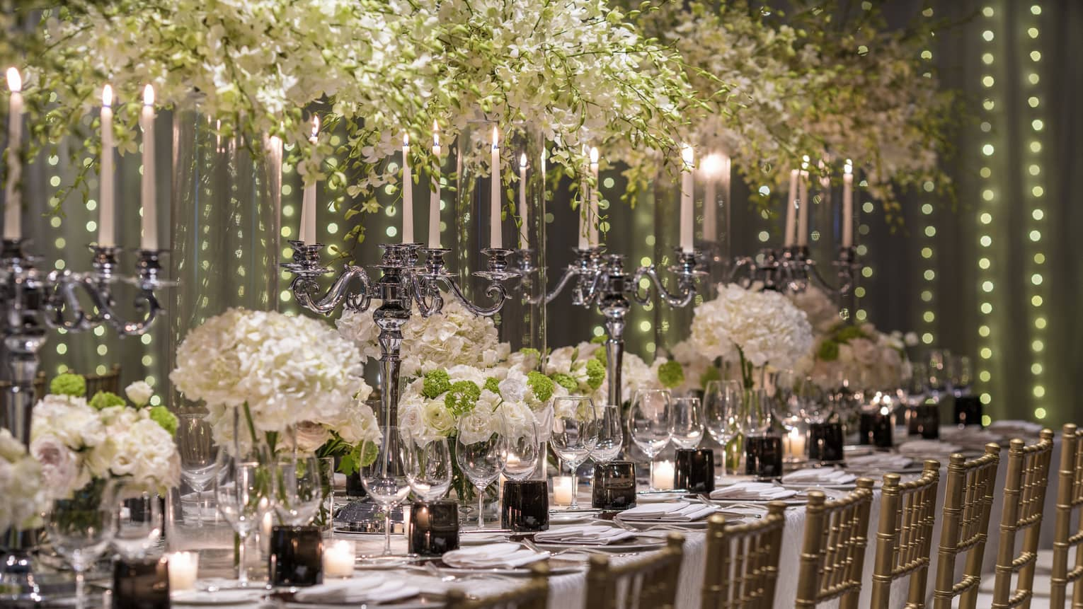 Elaborate white flowers and candelabras serve as the centerpiece of a dining arrangement