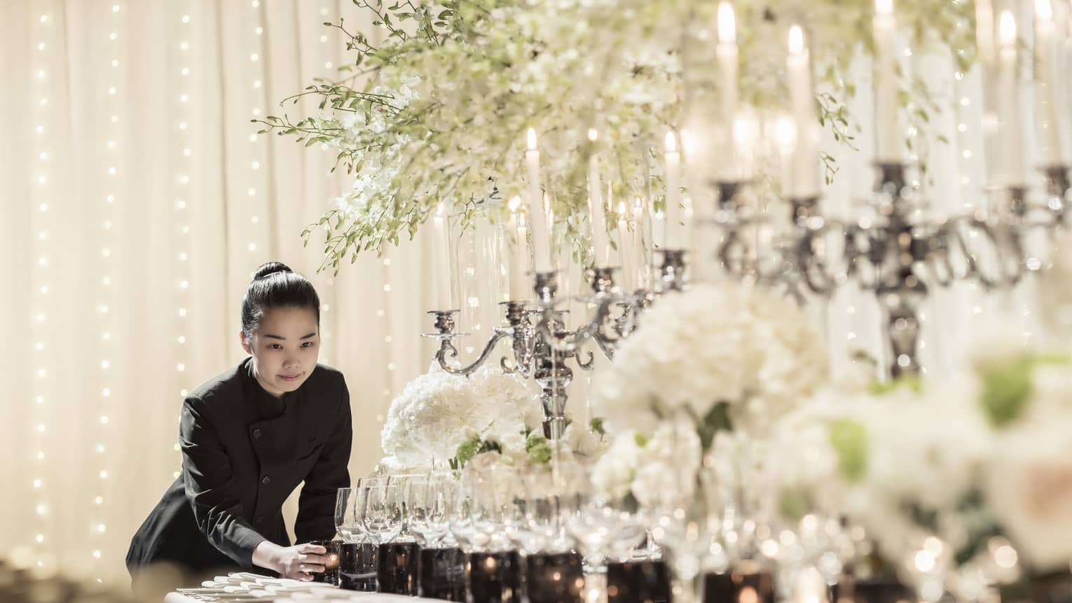 Hotel staff places candle at end of long formal dining table set with candlebras, sparkling lights