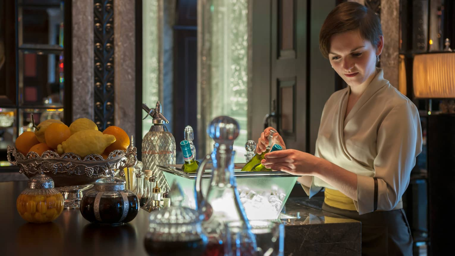 Woman in wrap dress reaches for Champagne bottle in dish on bar near bowl of fresh fruit