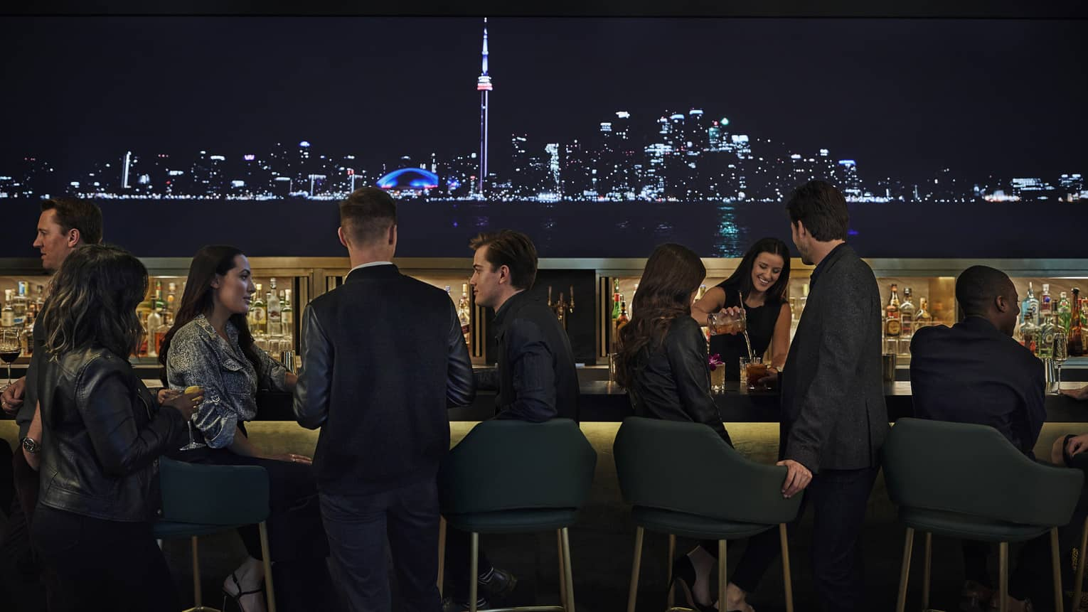 A lit up skyline of the city illuminate the bar, where guests sit and enjoy drinks