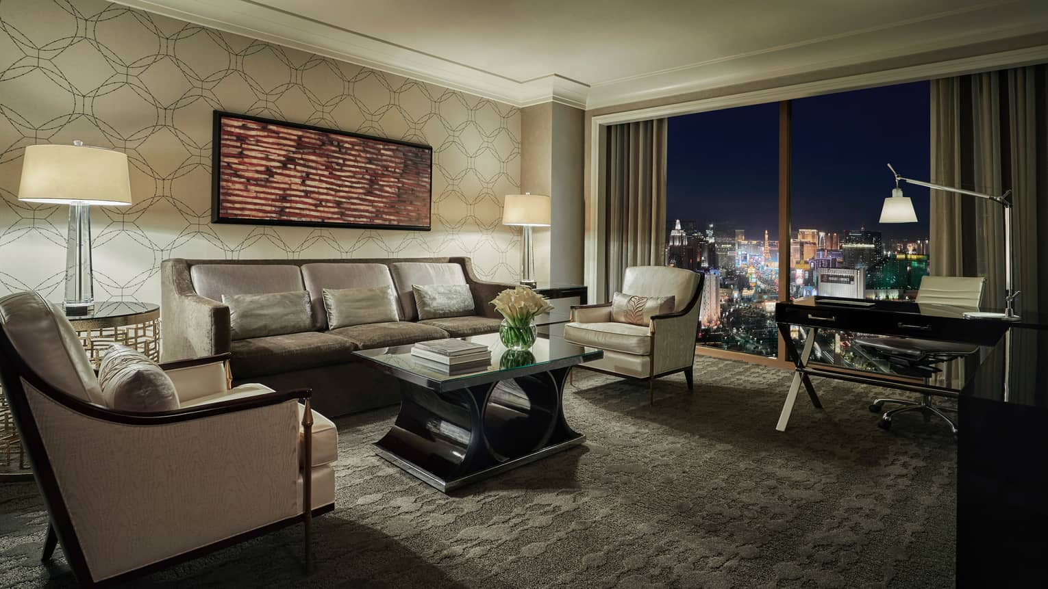 Strip-View Suite carpeted living room, desk by window overlooking Las Vegas strip lights