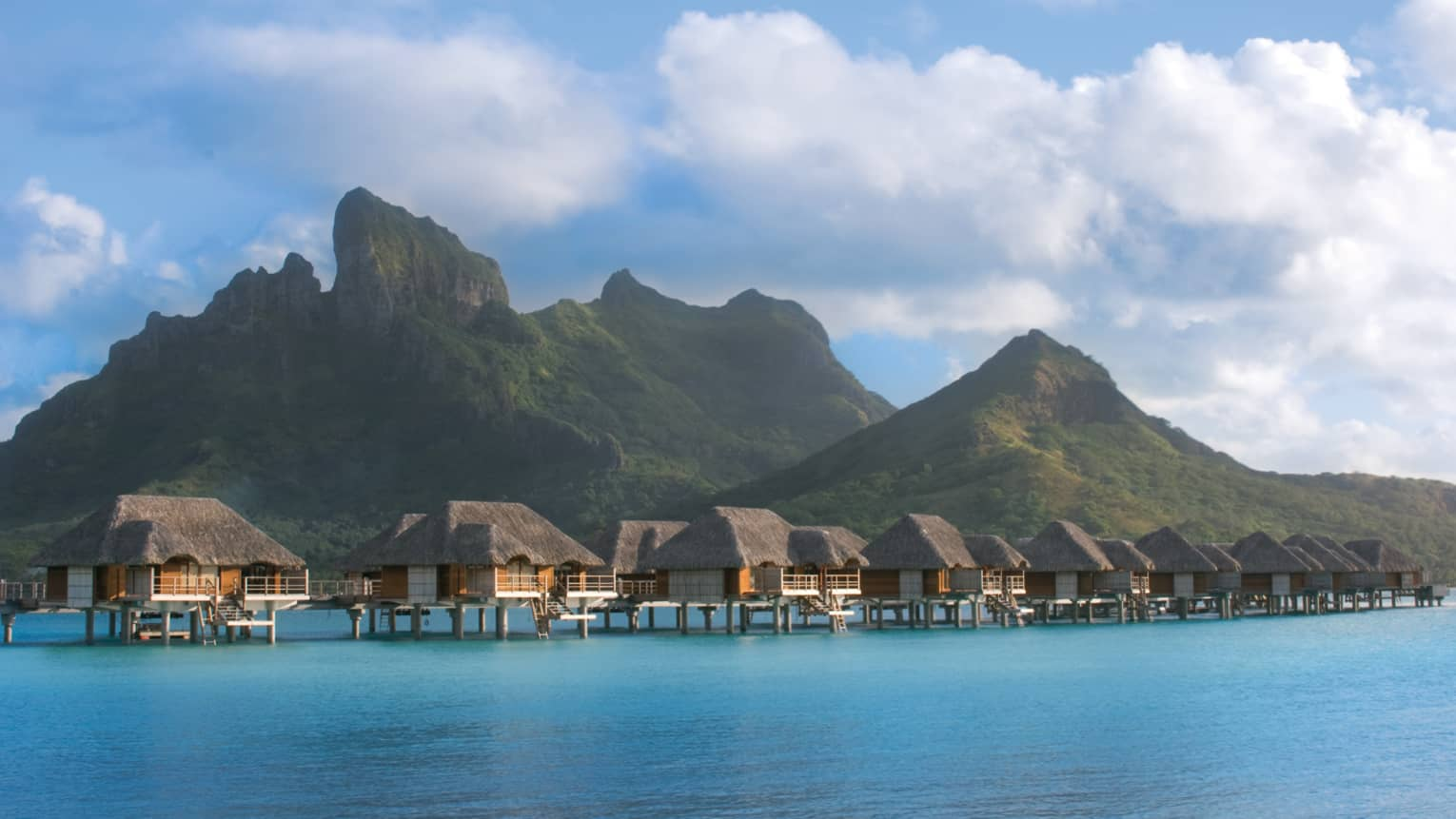 Two-bedroom overwater bungalows in a row over ocean with Bora Bora mountains in background