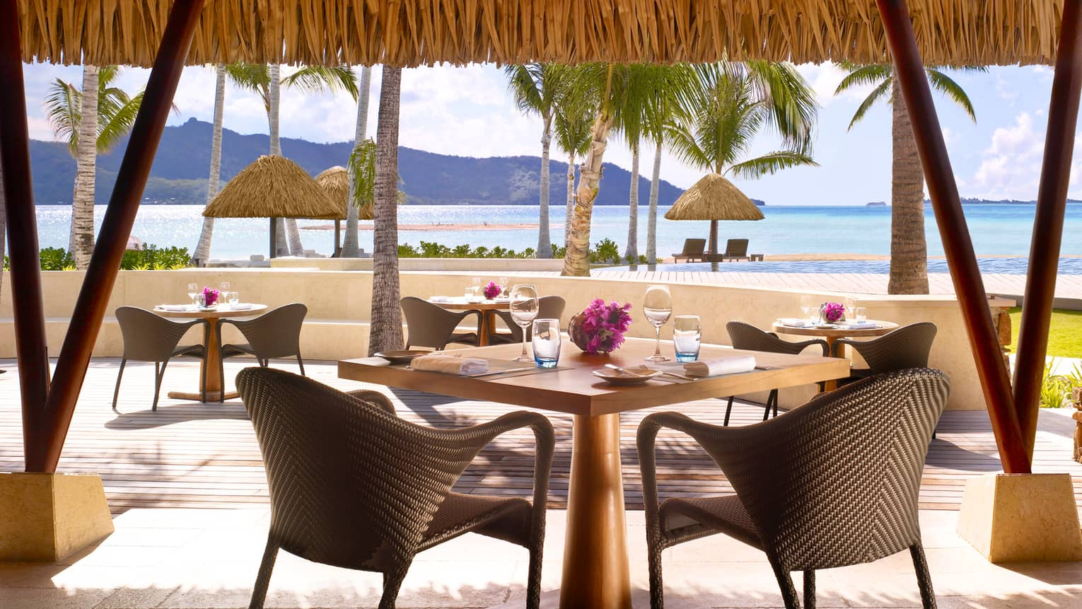 Tere Nui dining table with wicker chair looking out at sunny patio, ocean
