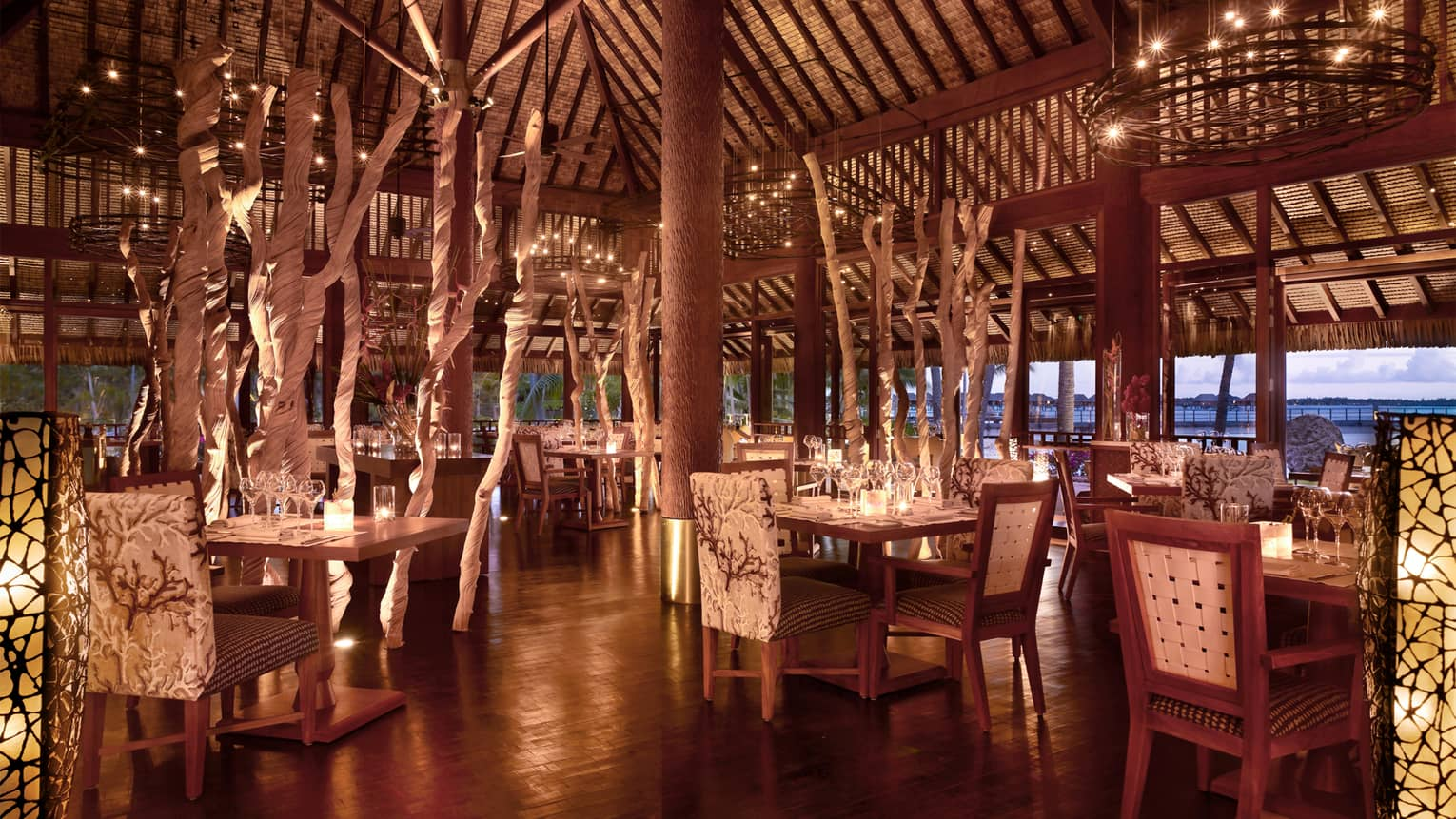 Elegant, candle-lit Arii Moana open-air dining room with plush chairs, decorative branches