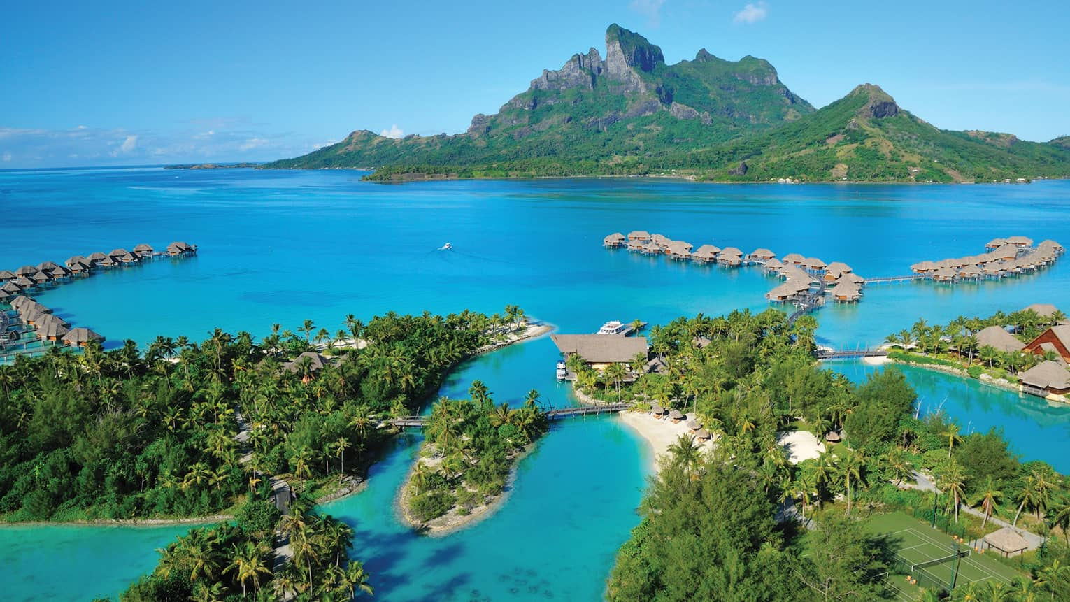 Aerial view of Bora Bora overwater bungalows in lagoon, mountain
