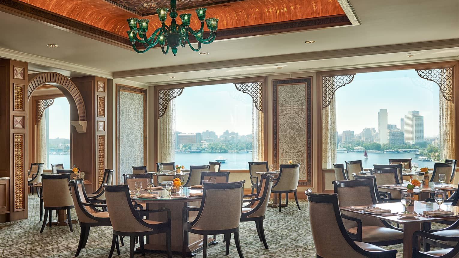 Zitouni Egyptian restaurant dining room tables with high ceilings and windows looking out at Nile river during day