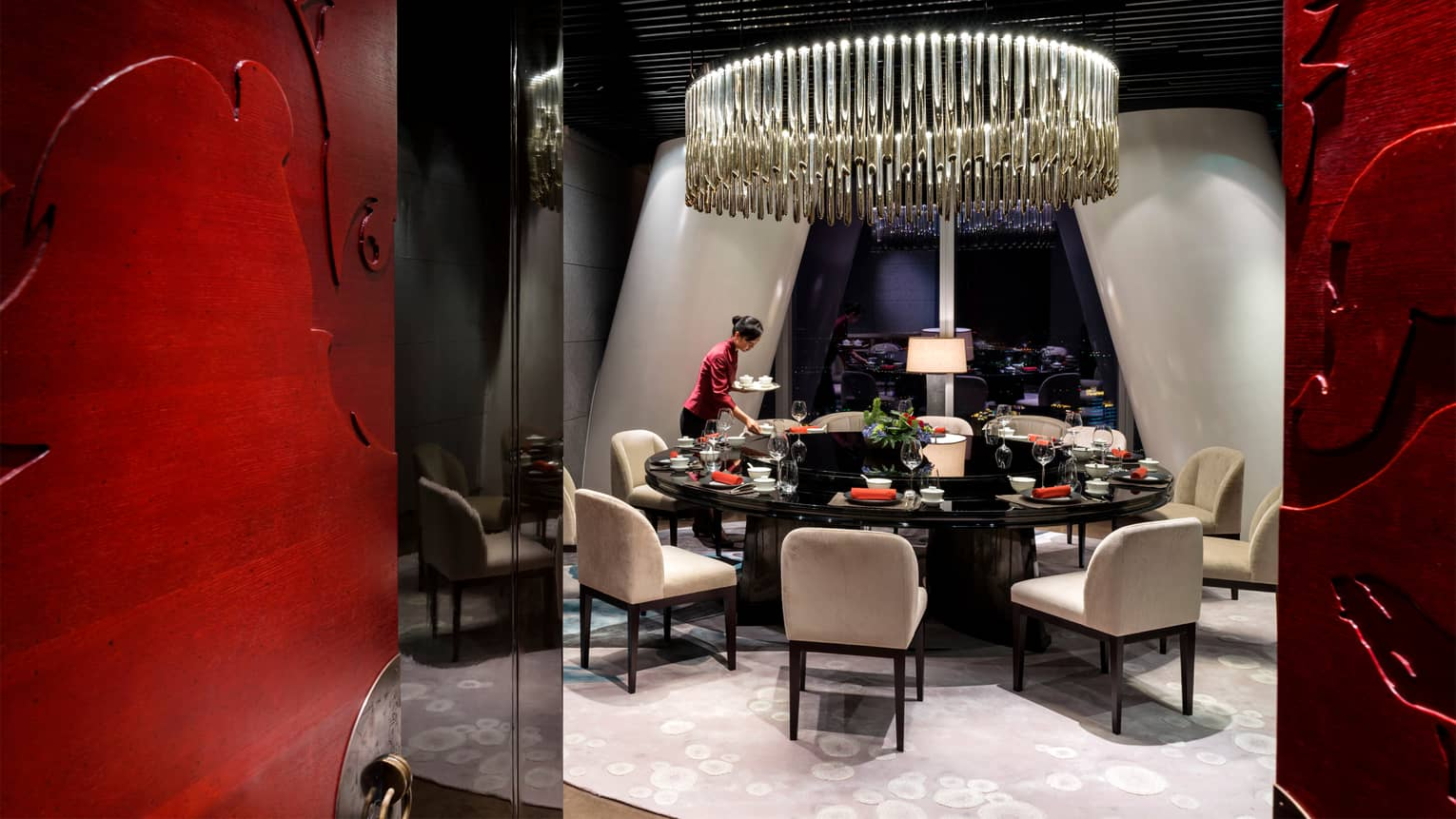 Yu Yue Heen server in red shirt sets round formal private dining table under large chandelier