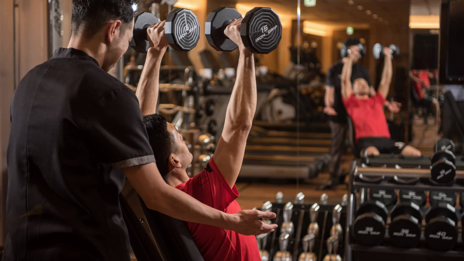Man in chair in front of mirror lifts two 15-pound weights above his head while personal trainer assists