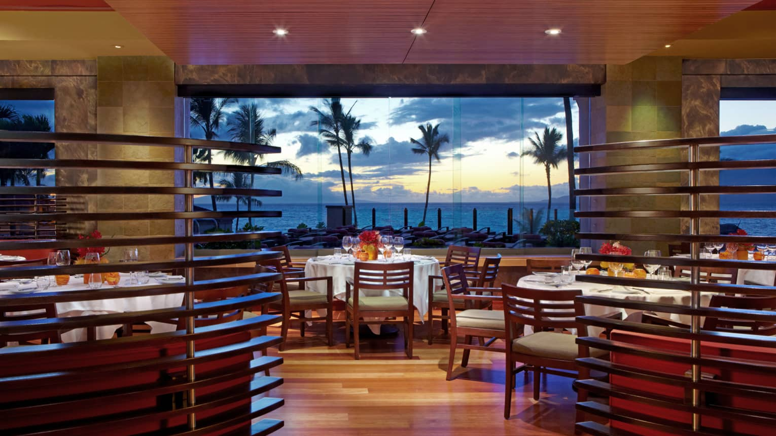 Spago dining room with wood decor, floor-to-ceiling windows looking out at palm trees, oceans and sunset