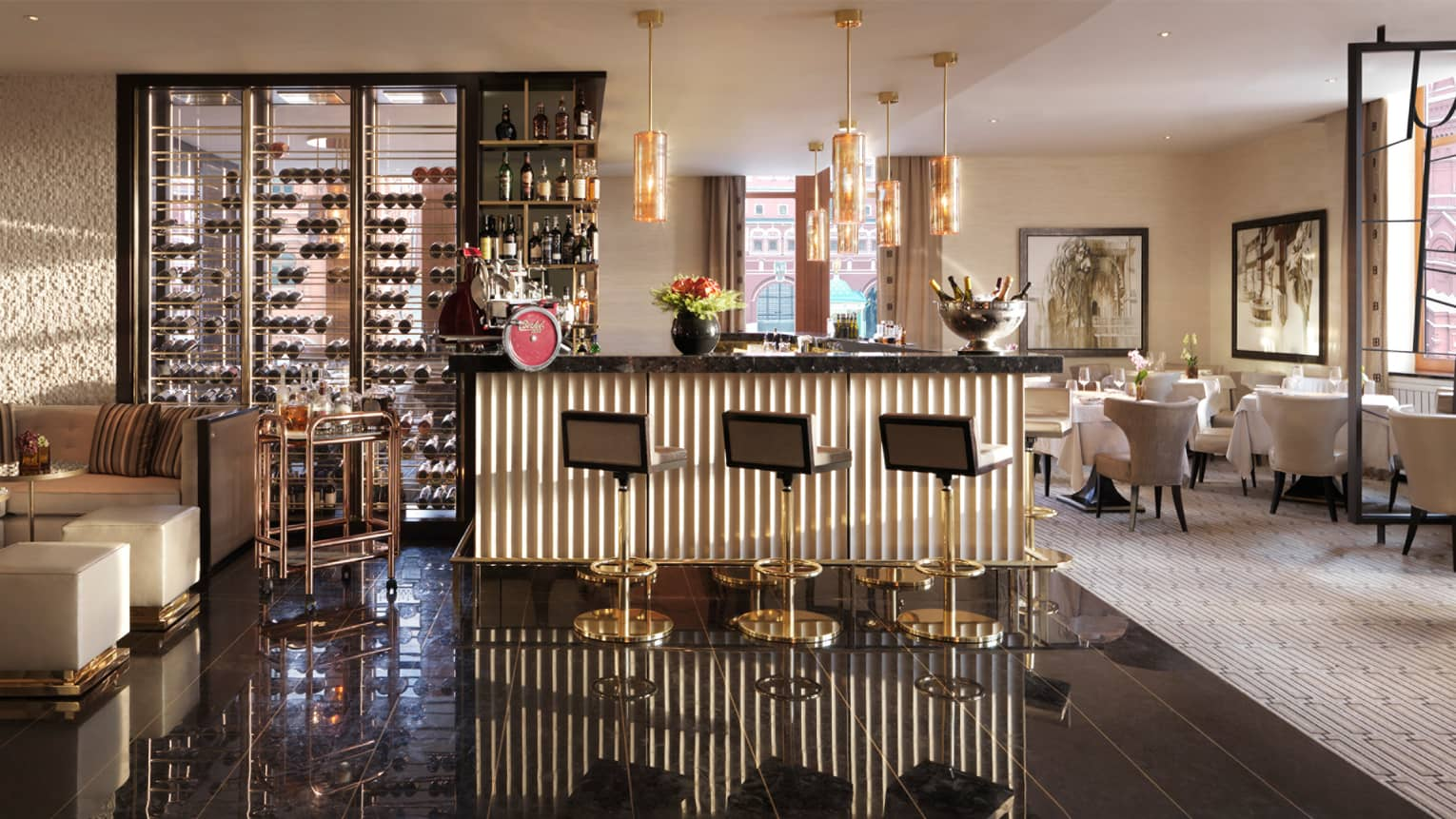 Quadrum restaurant dining room with small gold-and-marble bar with three stools, wine rack, Champagne on ice