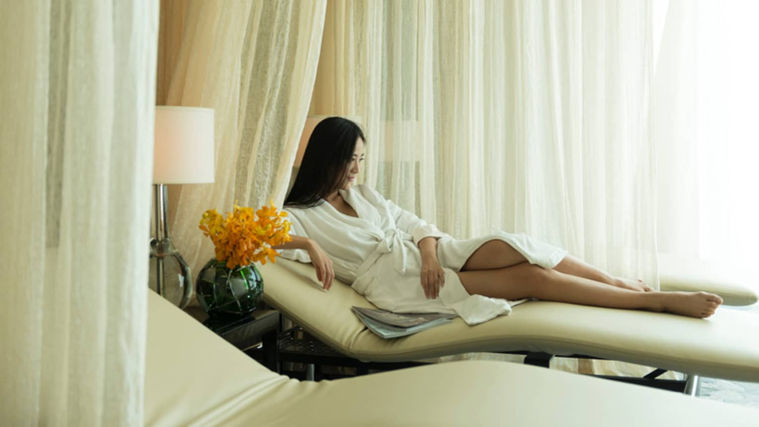 Woman wearing white bathrobe stretches out on white chaise lounge near white lamp, curtains
