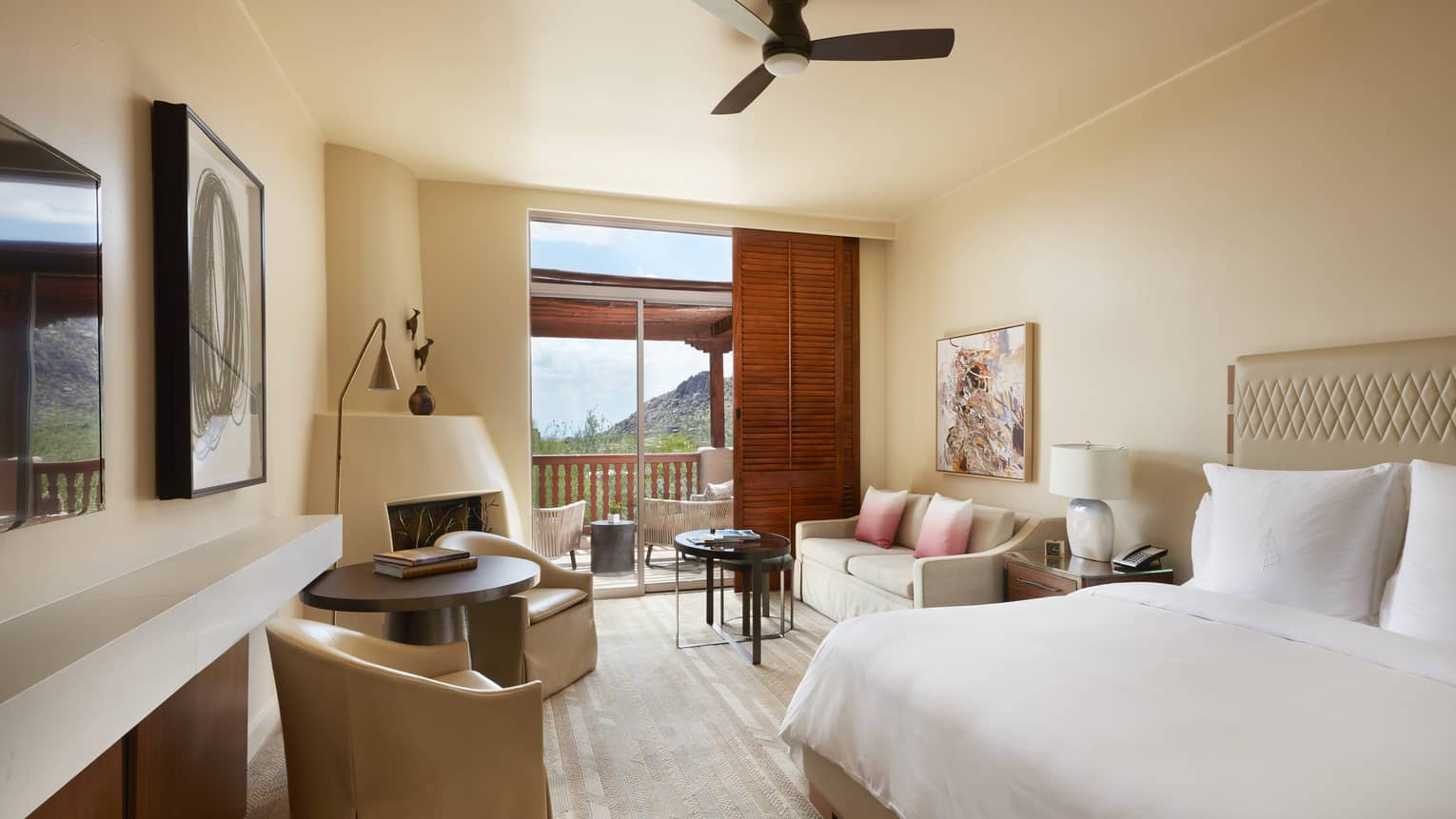Hotel guest room with king bed, two arm chairs and sofa, ceiling fan, walk-out patio