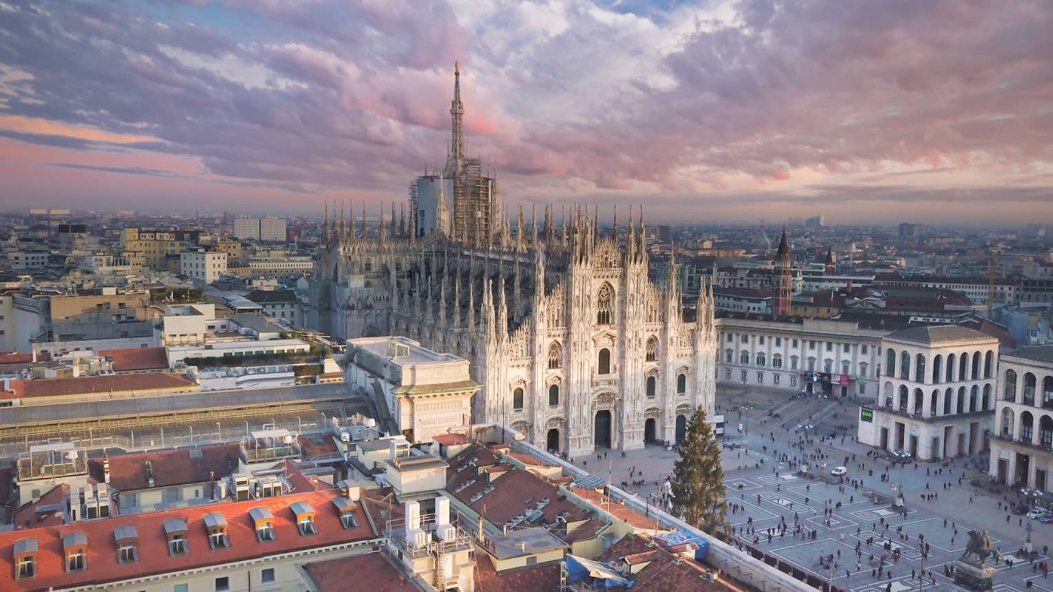 Aerial view of Milan, historic Duomo cathedral church towers at sunset