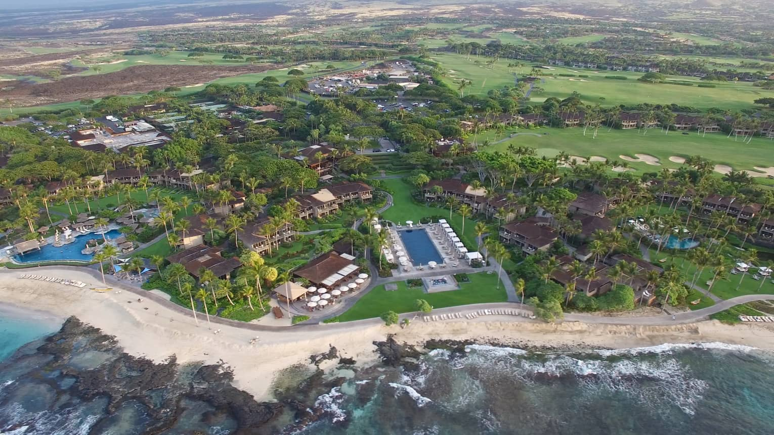 Aerial view of Four Seasons Resort Hualalai buildings, swimming pool, palm trees, beach, coast