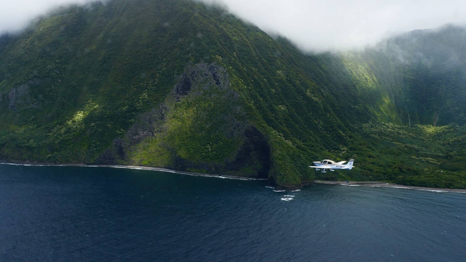 Small white airplane flies by large green mountain on Hawaii, Lanai coast