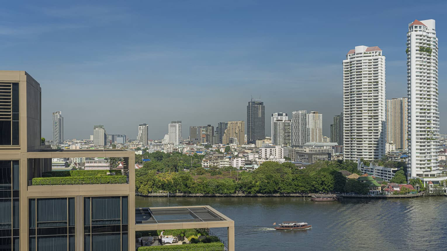 Hotel suites' outdoor patios, terraced on building, overlooking the Chao Phraya River and city