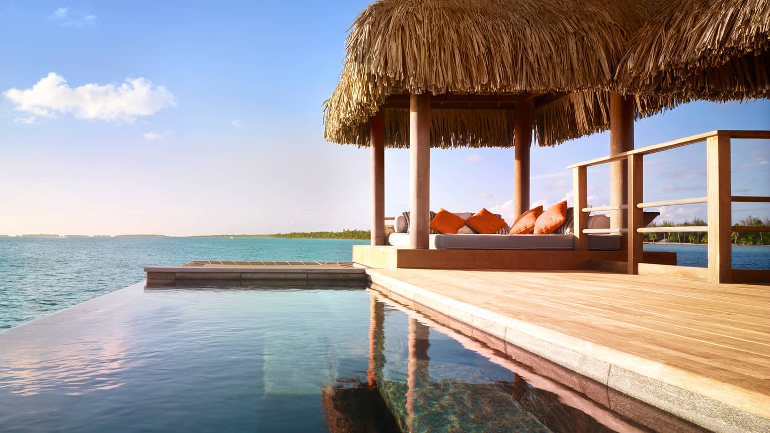 Overwater bungalow suite patio with infinity pool over ocean