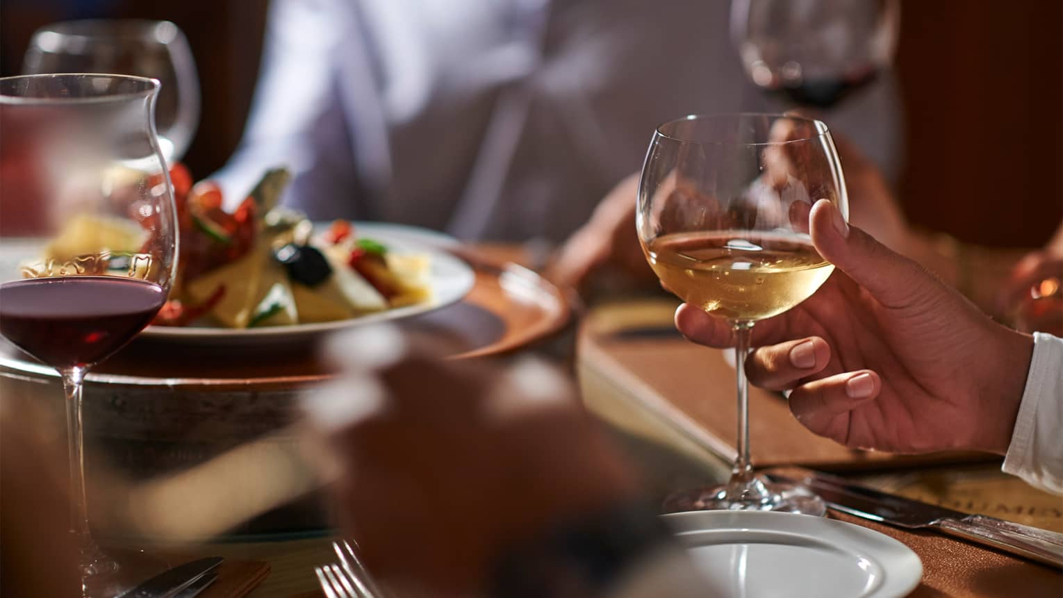 Close-up of man's hand holding a glass of white wine at formal dinner table