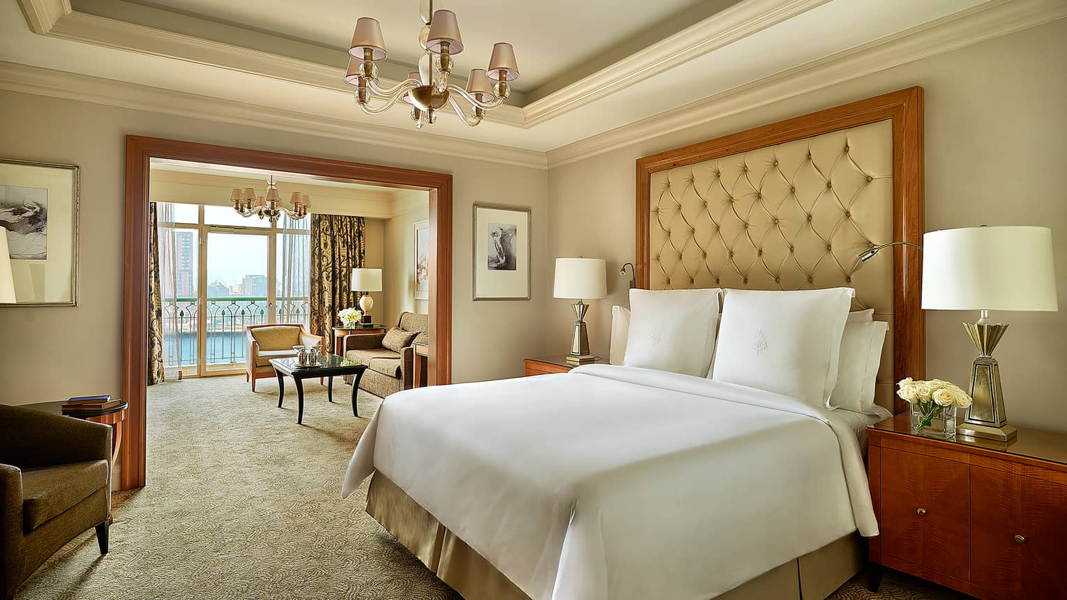 Premier Nile Room bedroom with cream and white tones, bed, high leather headboard, adjoining living room