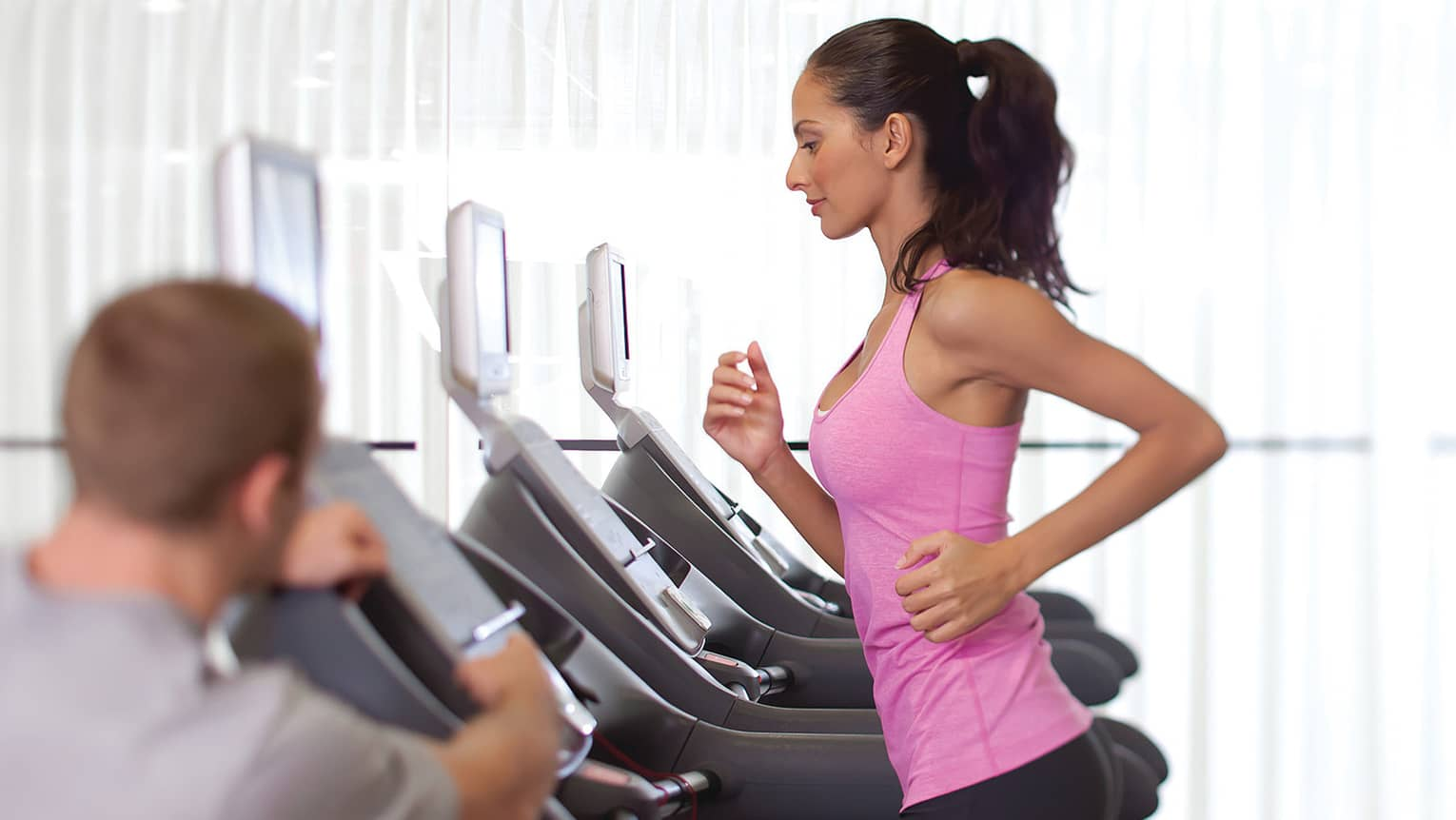 Woman in pink sleeveless shirt and ponytail runs on treadmill as personal trainer watches