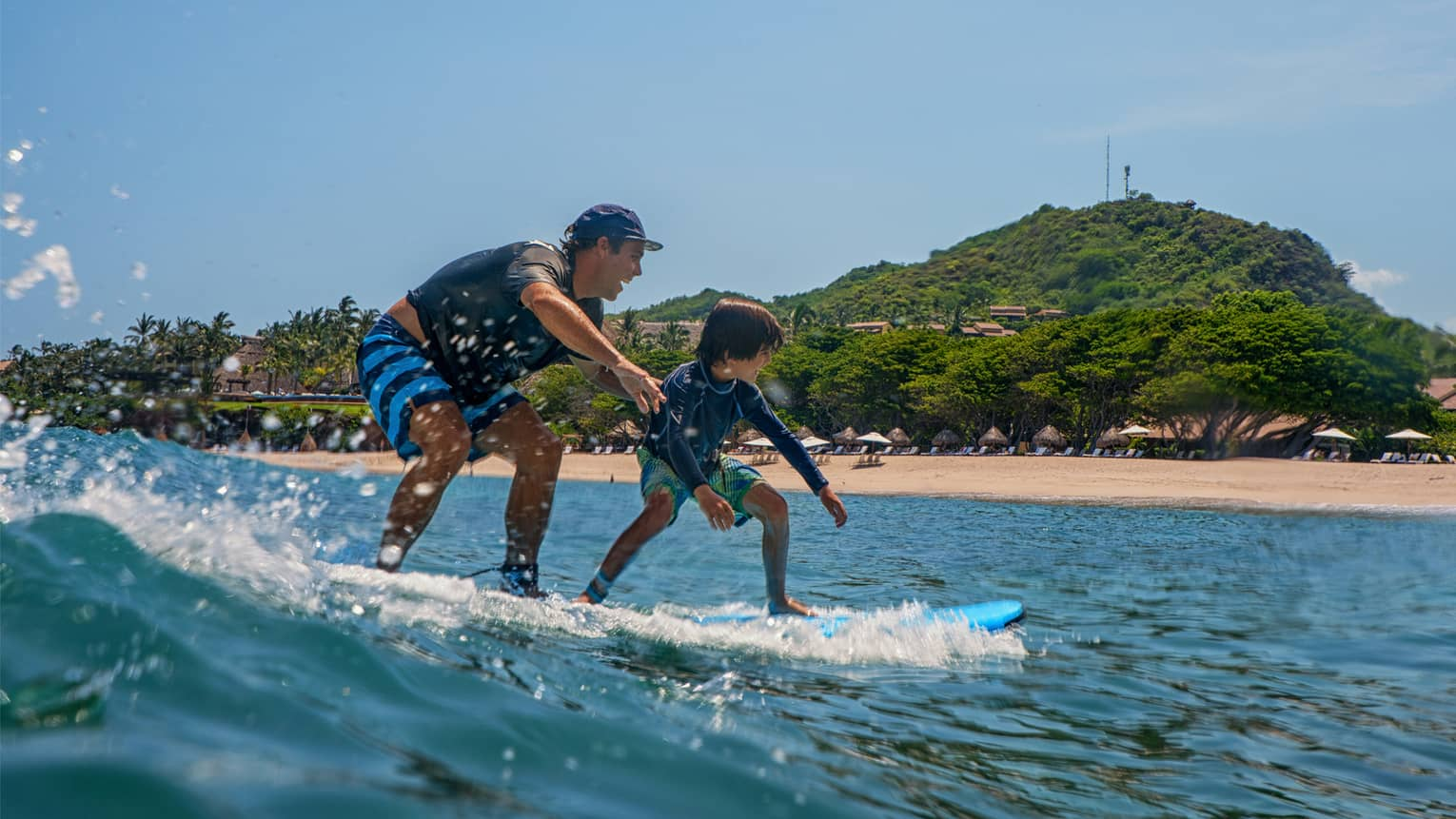 Man and boy balance on blue surfboard on wave, beach in background