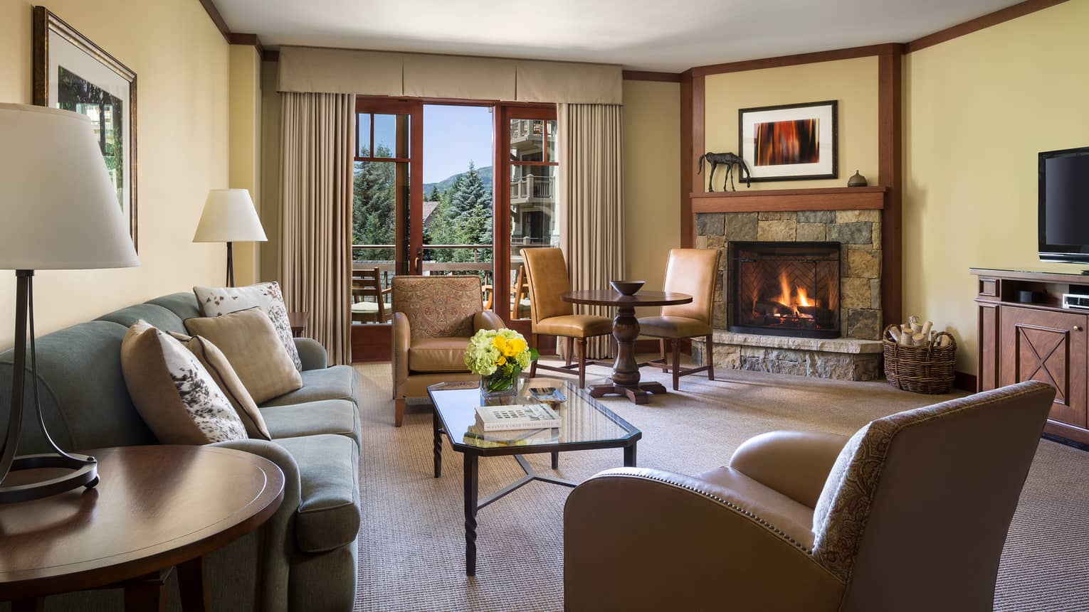 Deluxe Mountain-View One-Bedroom Suite separate living area with sofa, 2-seat dining table, fireplace
