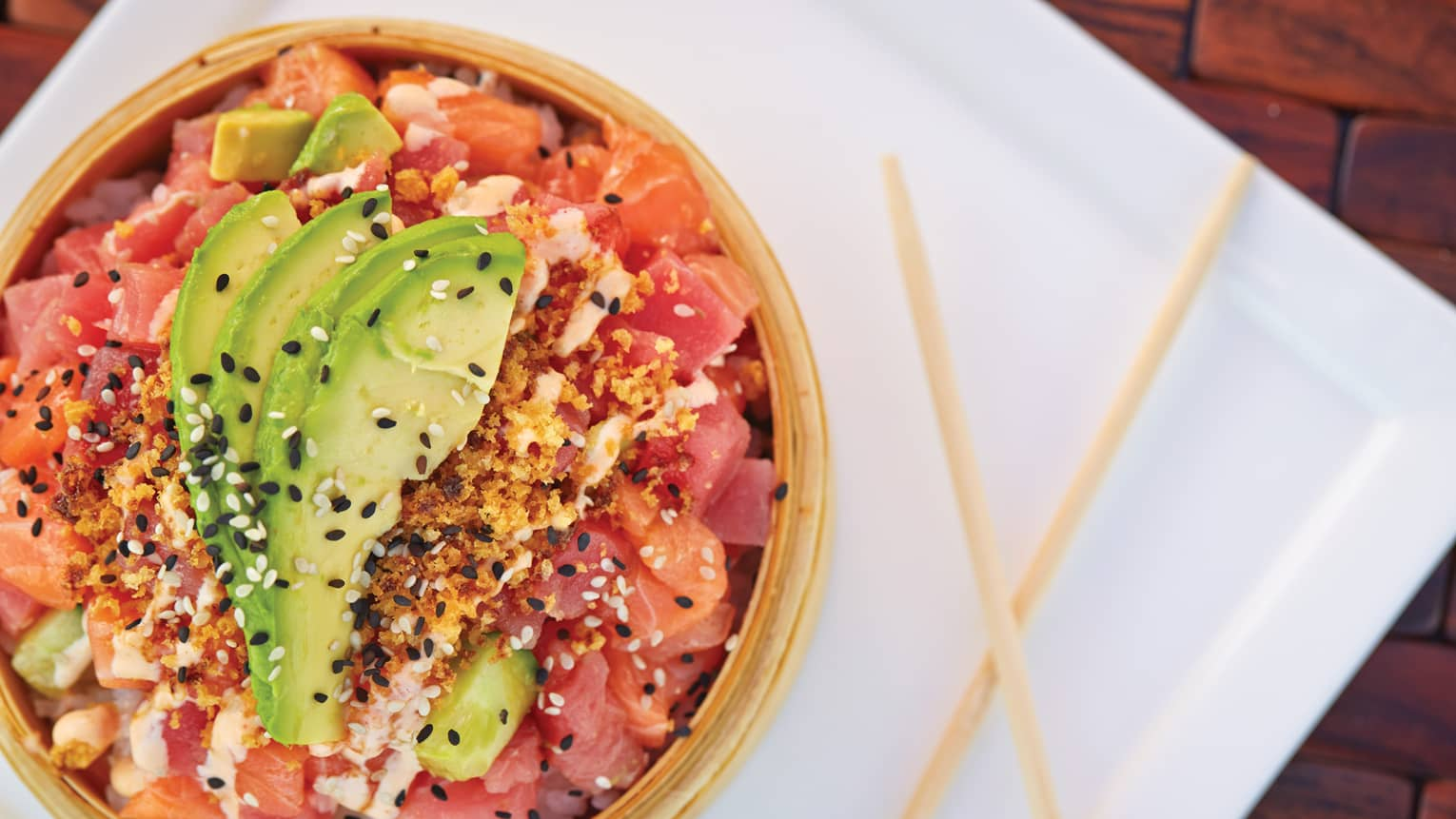 A poke bowl is topped with avocado slices and sesame seeds