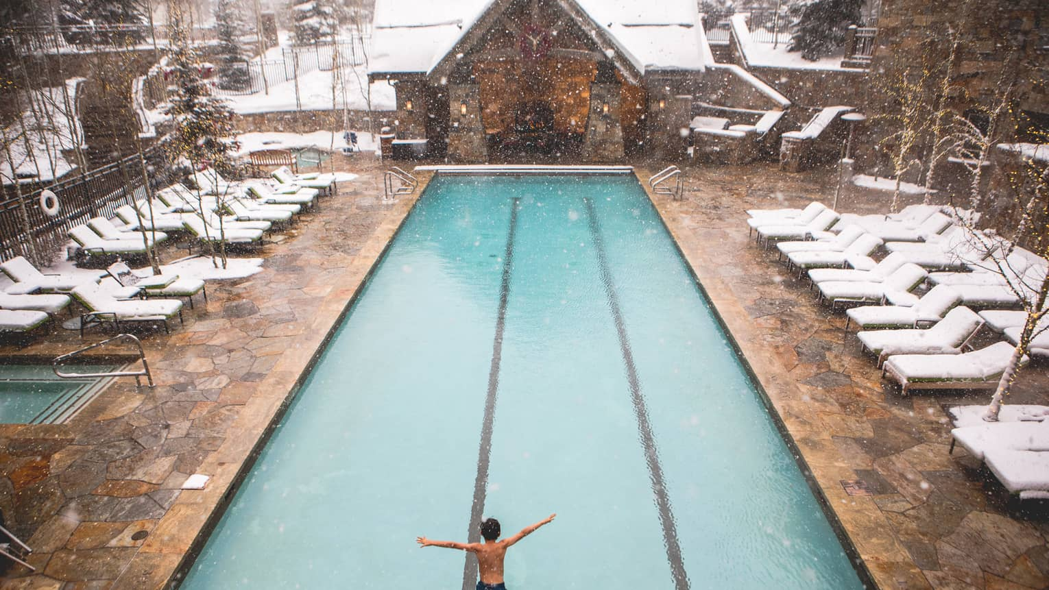 Two children jump into the heated pool on a snowy day at Four Seasons Vail