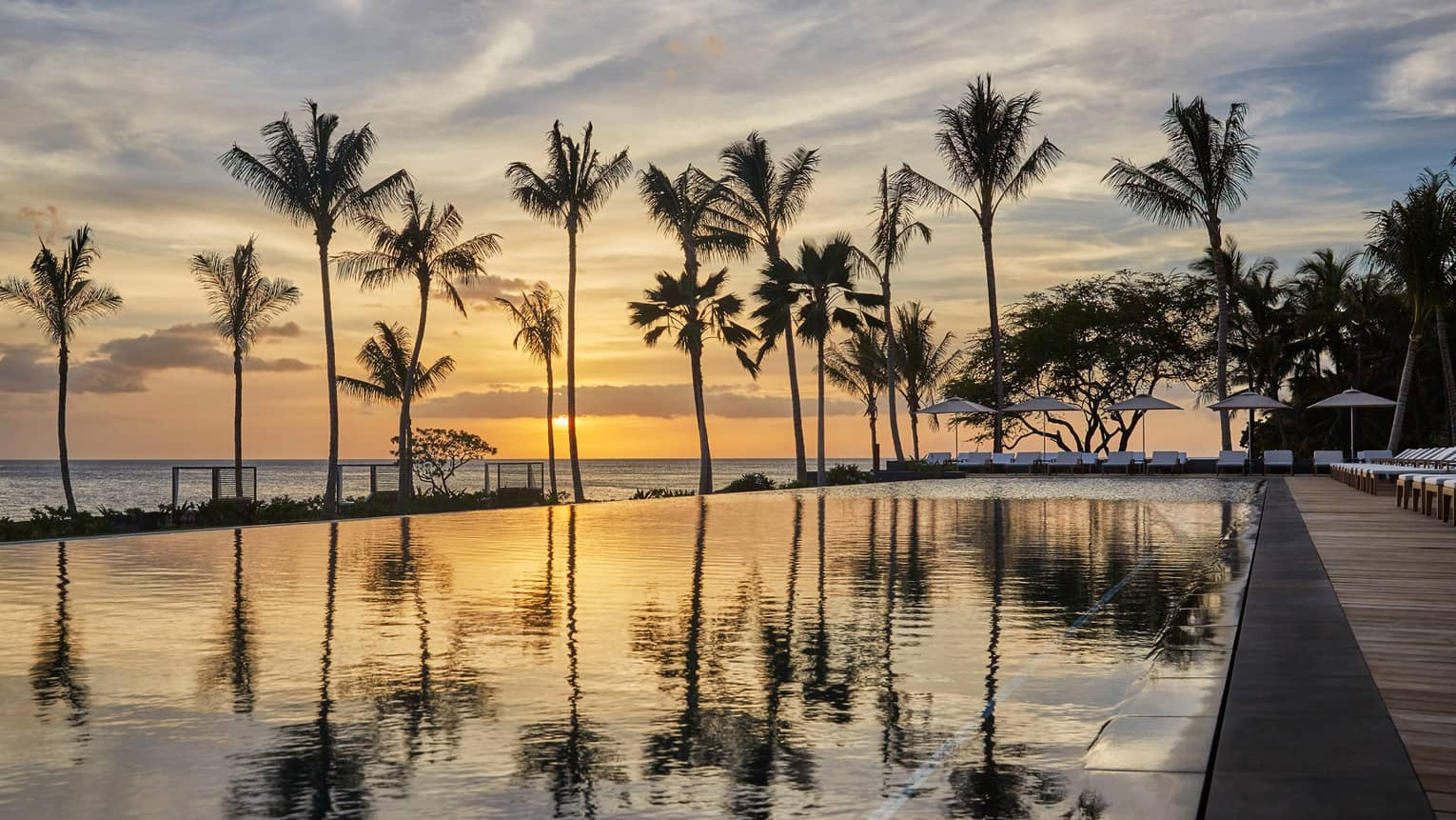 Silhouettes of tall palm trees reflected on outdoor swimming pool against orange sunset