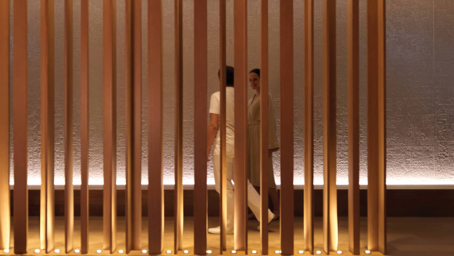Spa staff, woman in white bathrobe walk down hall behind panel wall with lights