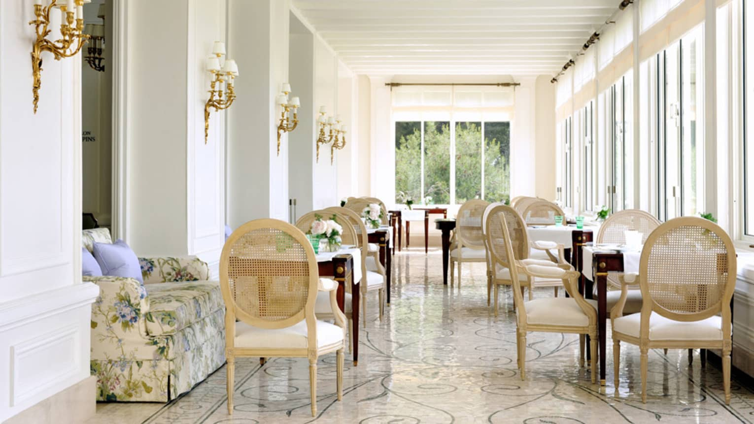 Le Veranda dining chairs around tables in restaurant sunroom