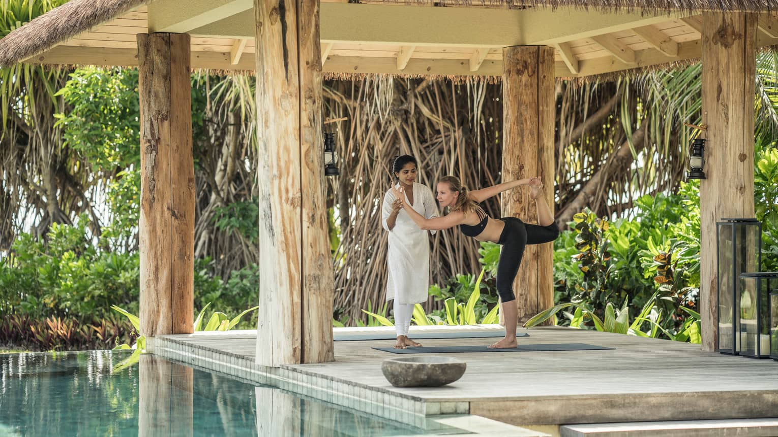 Yogi assists woman with yoga pose under thatched roof gazebo by plunge pool