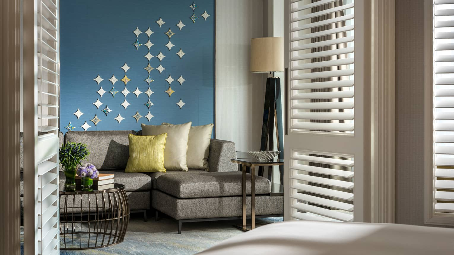 Gold pillows on grey sofa against blue wall with star-shaped Peranakan tile mural
