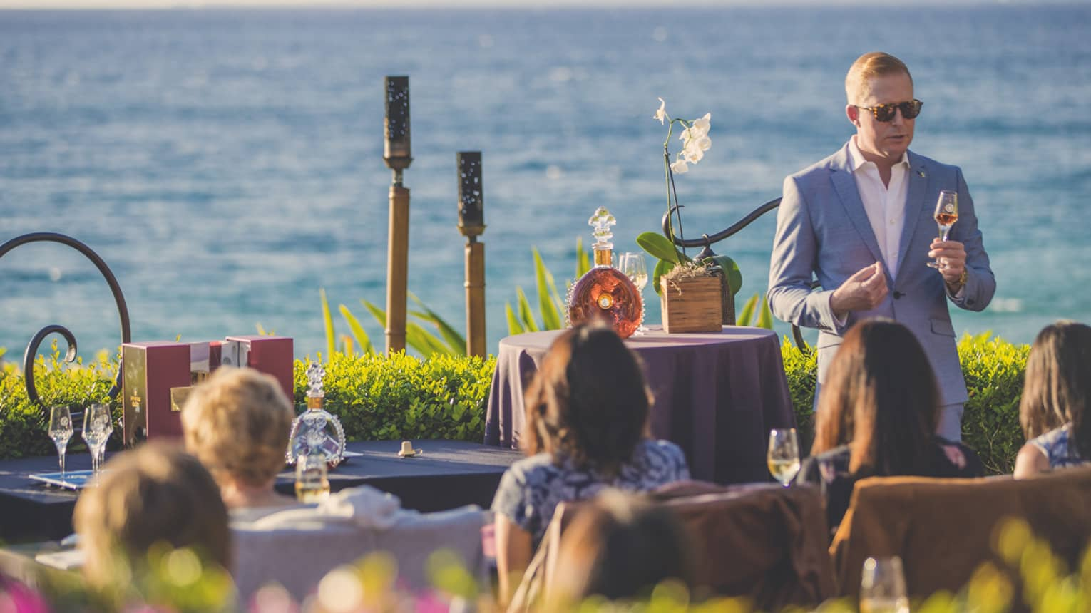 Guests seated outside by the beach listen to a presentation by a wine sommelier