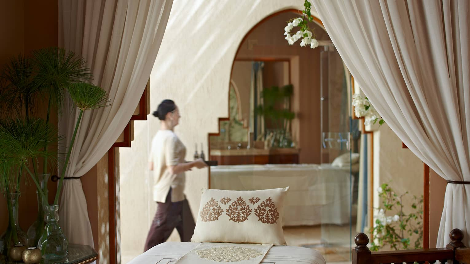 Woman with tray walks behind massage bed with embroidered pillow in spa