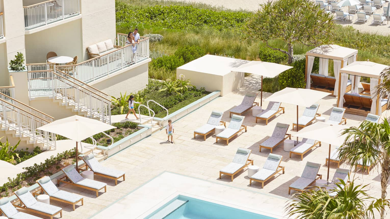 Plush lounge chairs and square umbrellas are arranged around a pool