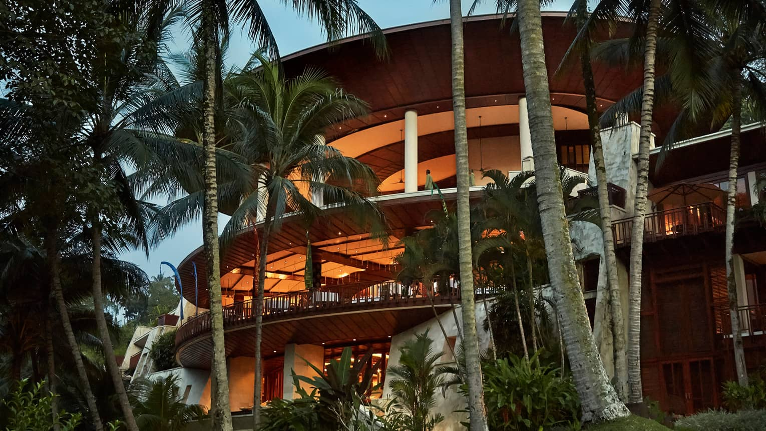 Four-storey curved balconies around resort building at dusk, lit with orange lights, surrounded by palms